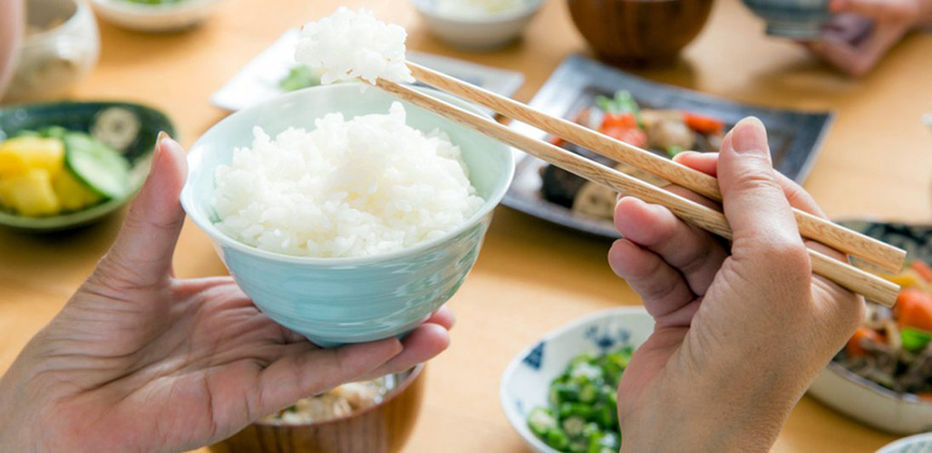 holding bowl of rice and chopsticks at Japanese eating table