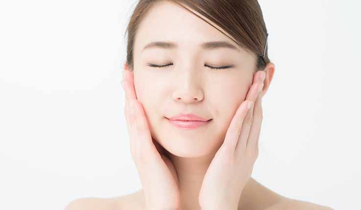 Japanese woman applying camellia oil to face and neck