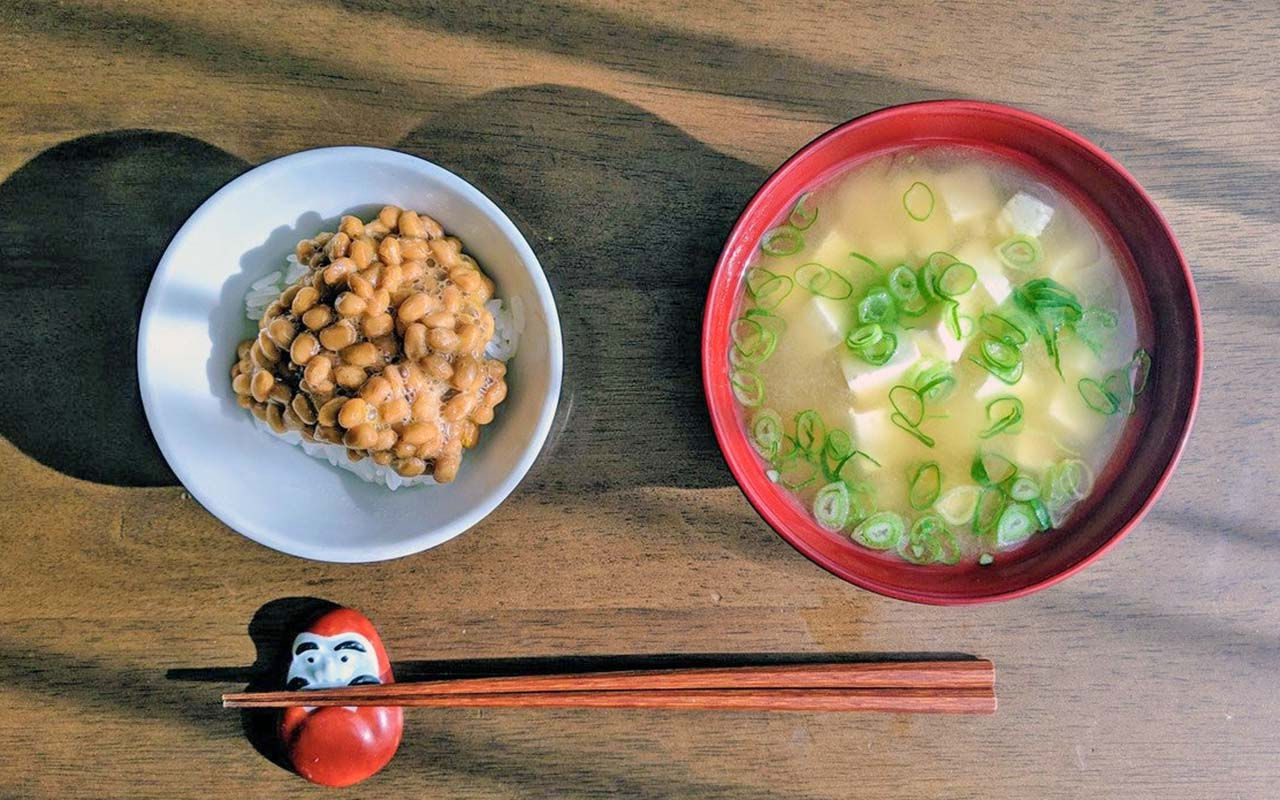 Chopsticks, natto (fermented soybeans) over rice and tofu miso soup on a wooden table