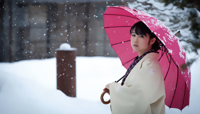 Japanese lady holding umbrella on a snowy winter day