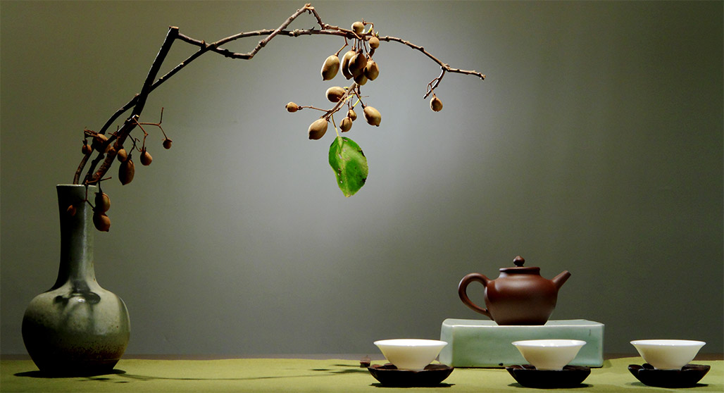 Teapot and cups and earthen pot with a branch bearing leaves and fruit