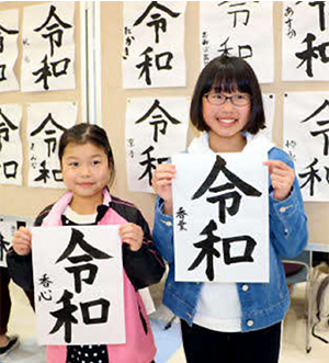 Two girls holding papers with Reiwa calligraphy in front of a bulletin board