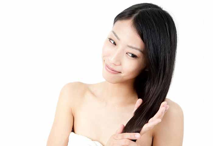 Japanese woman in bathrobe caring for hair