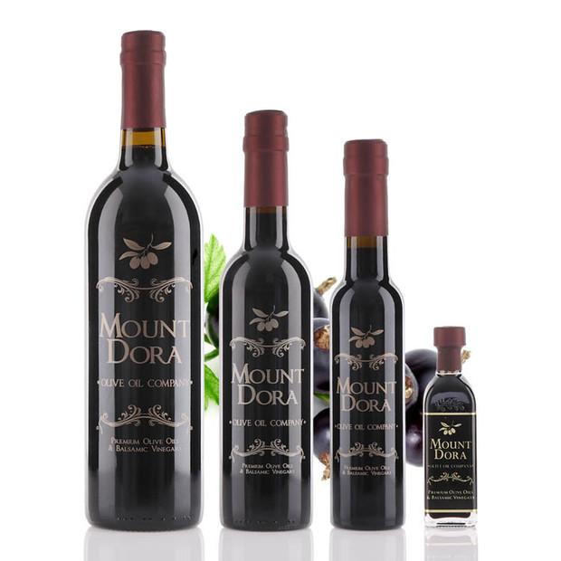 Four different size bottles of Mount Dora Black Currant Dark Balsamic Vinegar