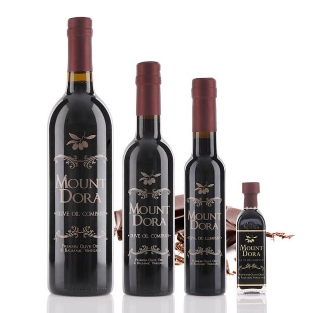 Four different size bottles of Mount Dora Dark Chocolate Dark Balsamic Vinegar