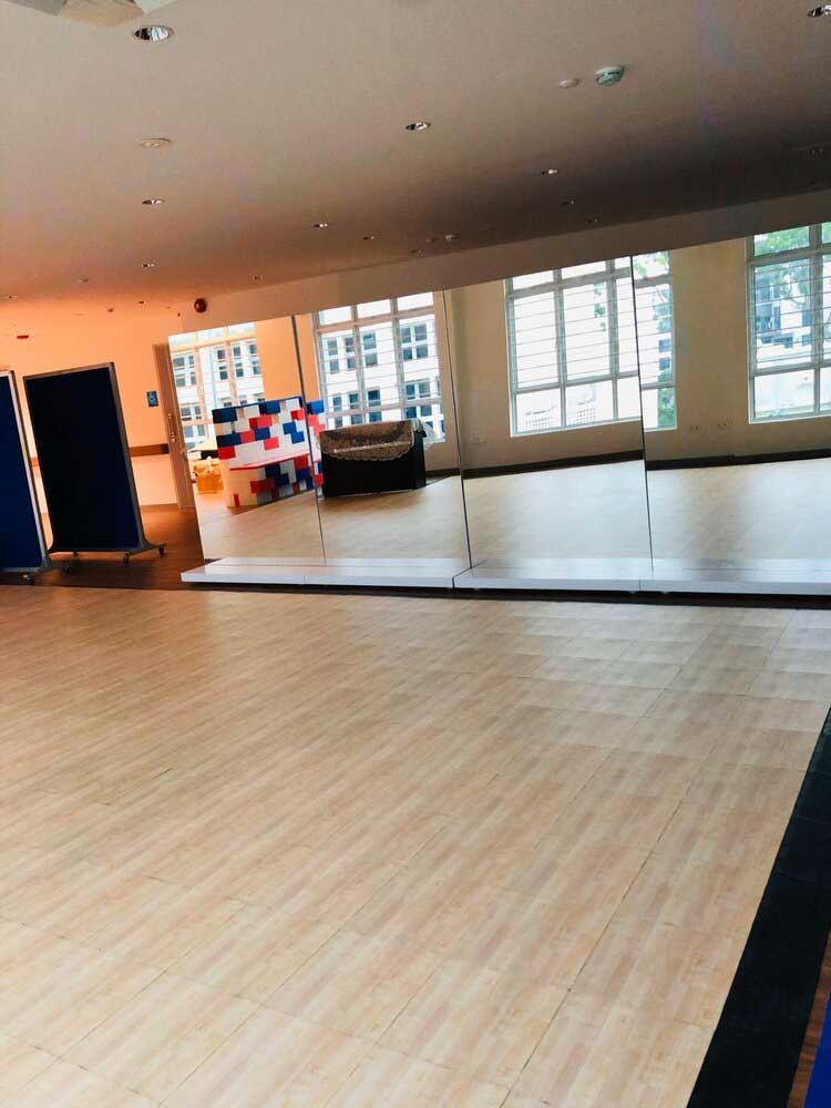 Setup the dance studio using tiles with a light wood parquet finish