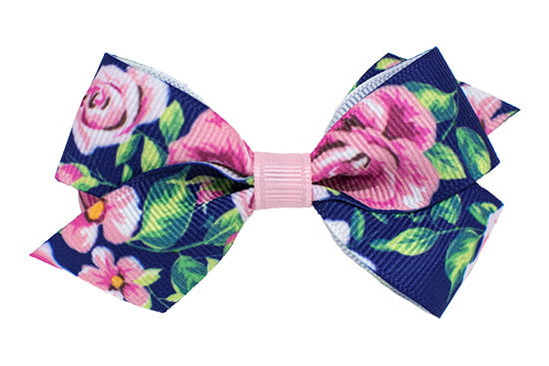Navy floral printed butterfly bow with a flat light pink center, shown on a bitty clip