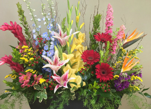 """Our """"Rainbow of Love"""" design is a unique way to express your love. It features a variety of flowers from tropical Birds of Paradise, Gingers, to Roses, Stock, Gladiolas and Gerbera Daisy's."""