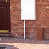INSUduct on a property wall next to an electric meter box and door.