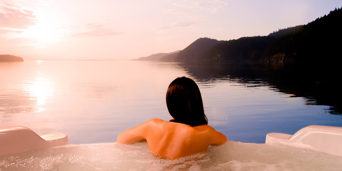 Woman relaxing in a Coast Spas, Infinity Edge Spa overlooking a mountain range, forest and mountain valley lake.