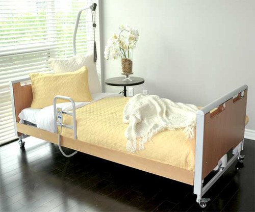 The Invacare ETUDE-HC longterm care hospital bed is designed for both home care and facility use. Shown with optional Side Rail Support, Lifting Support Trapeze, and decorative Beech Accent Panels. (Bedding, pillows and side table sold separately)