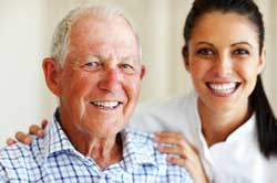 Vertical photo of a white haired man approximately 70 years of age with his 30-something female caregiver. Both are smiling and exhibiting how NewLeaf cares deeply about our customers.