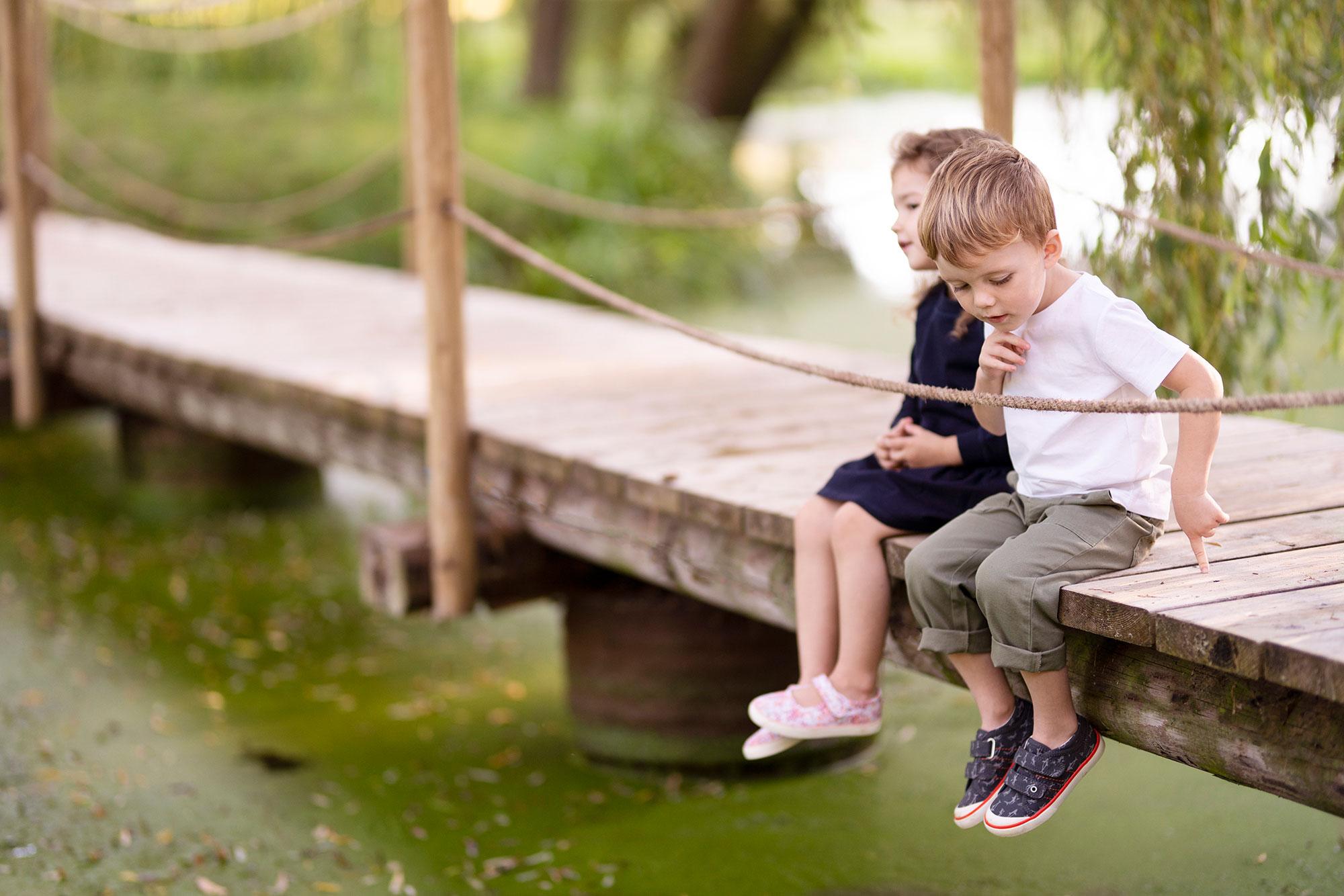 Girl and Boy Sitting on Bridge