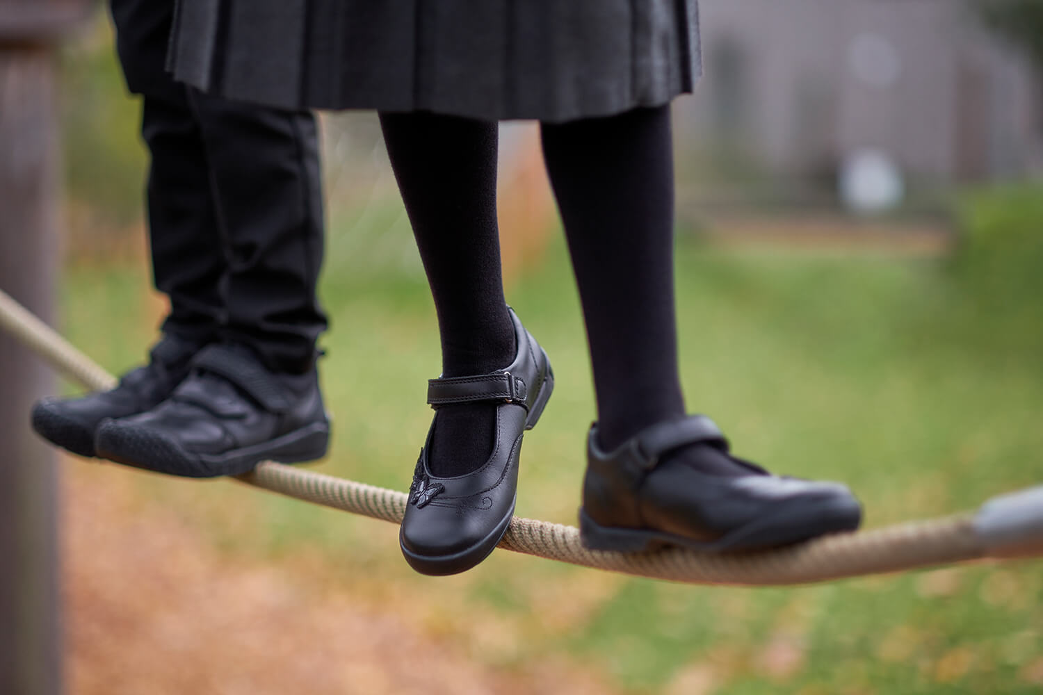 Girl and boy in school shoes on rope