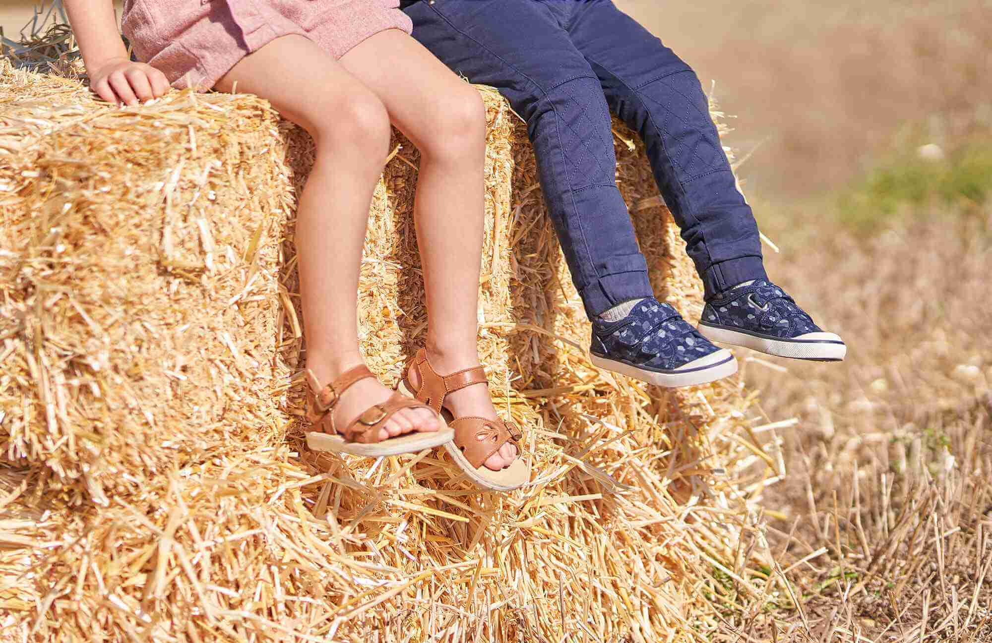 Girl and boy sitting on hay bale