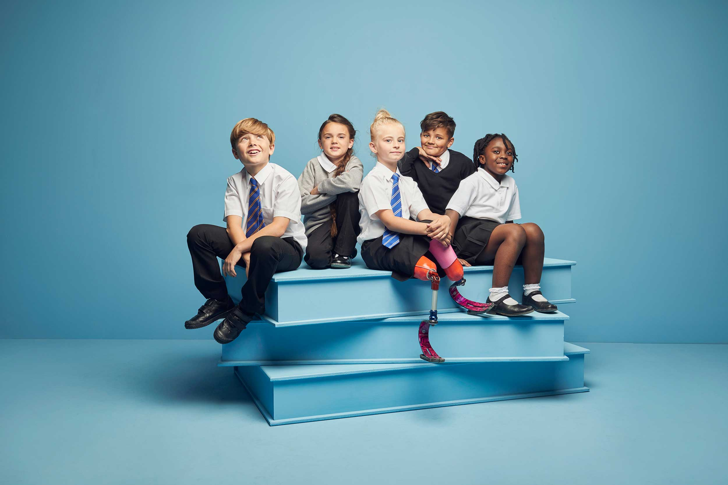 Kids in school uniform sitting on books