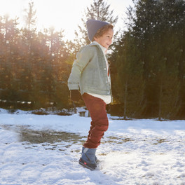 Child wearing Baker Waterproof/Insulated Blue Boots outdoors with snow on the ground.