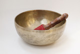 "A rare, genuine hand made, hand hammered medium/large sized brass singing bowl.   Comes with matched red suede covered wood stick (stick may not be the exact one pictured here).  The stick used to create a cool and sweet humming tone from the bowl.  To generate the tone, the stick is firmly rubbed in a continuous motion against the exterior rim of the bowl.  A tone with some variations in the harmonics is produced.    The stick can also be gently tapped on the rim of the bow to create a sonorous bell tone.  Both methods of sound generation are utilized for meditations, yoga, and just because it is a cool and pleasing sound!  Rich tenor tone on this one.    1.5 kg  4""H  9""W   TM55655"