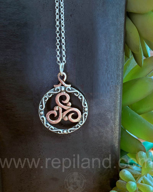Ciùnas Triskele Pendant, sterling circular frame with beads and scrolls around a gold triskele.