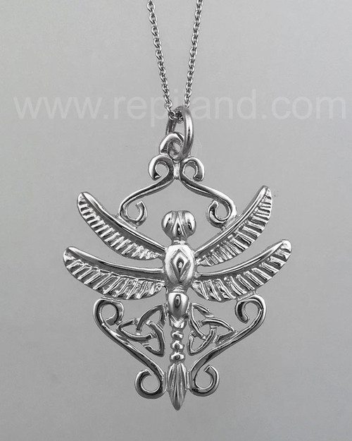 A dragonfly with trinity knots and scrollwork. White gold.