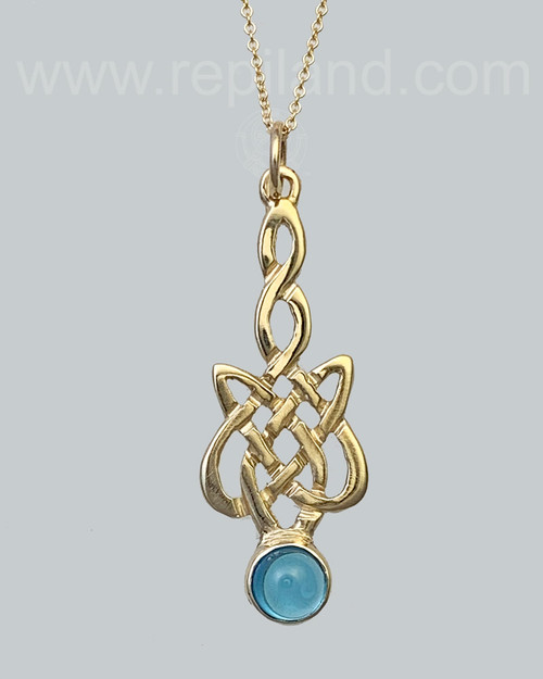 The Sionnach Gem Pendant has a twined stem that drops into a wider knot below with a 6mm gem at the bottom. Yellow gold with Blue Topaz.