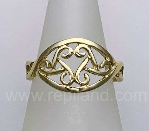 The Caryll Ring features an almond shape frame with 2 triskeles touching inside, creating a heart shape. Pictured in yellow gold.