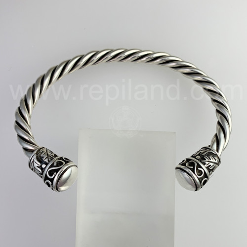 The Oak Leaf Wrist Torc features infinity symbols and oak leaves with a smooth polished end cap.