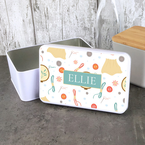 Personalised storage tin with sewing thread design.