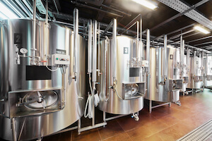 Inside of a brewery with lots of stainless steel vats in view