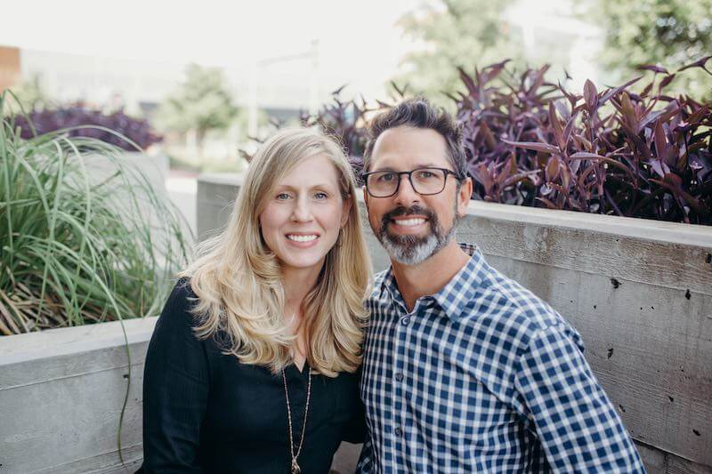 Derrick and Keri Holder, owners of Waterloo Paneling, sitting close together with smiles on their faces in an outdoor setting with planters full of greenery behind them