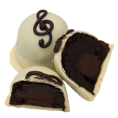 """Chocolate Symphony Dessert Truffle  """"Ebony and Ivory live together in perfect harmony…"""" as sung by Paul McCartney and Stevie Wonder  Our Dark Chocolate Truffle Ganache is paired with an Extra-Bittersweet 75% Dark Chocolate Ganache center.  If you are worried that going to this extreme Dark Side will be too much for you… don't; the creamy white chocolate cover is your sweet salvation.   The bitter dark inside and sweet white outside work together to hit just the right notes.  This Special Edition is too good to last!"""