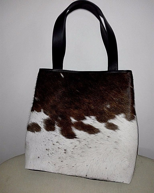 A beautiful cowhide tote bag made from real and natural fur in spotted brown and white, it has soft premium leather handle and two small pockets inside.