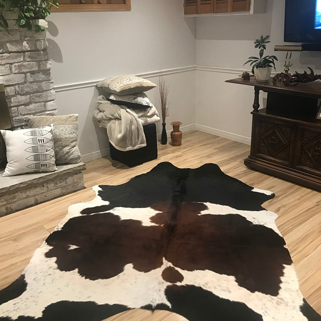 The caramel browns black speckled or salt pepper cowhide rugs are beautiful and really bring a beautiful richness to the room, no need for underneath.