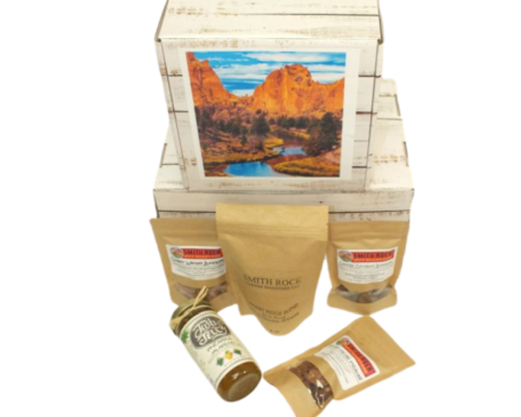 Smith Rock Gift Box includes Smith Rock Nut Roasters - Coffee Coconut Almonds, Salted Pecan Praline and Sweet Whisky Almonds made with Pendleton Whisky, Smith Rock Coffee Roaster - Misery Ridge Blend and Justy's Pepper Jelly - Pineapple Pepper Jelly - Mild.  Designed in a custom Smith Rock Theme gift box with hand made bow.  Available for same day delivery.