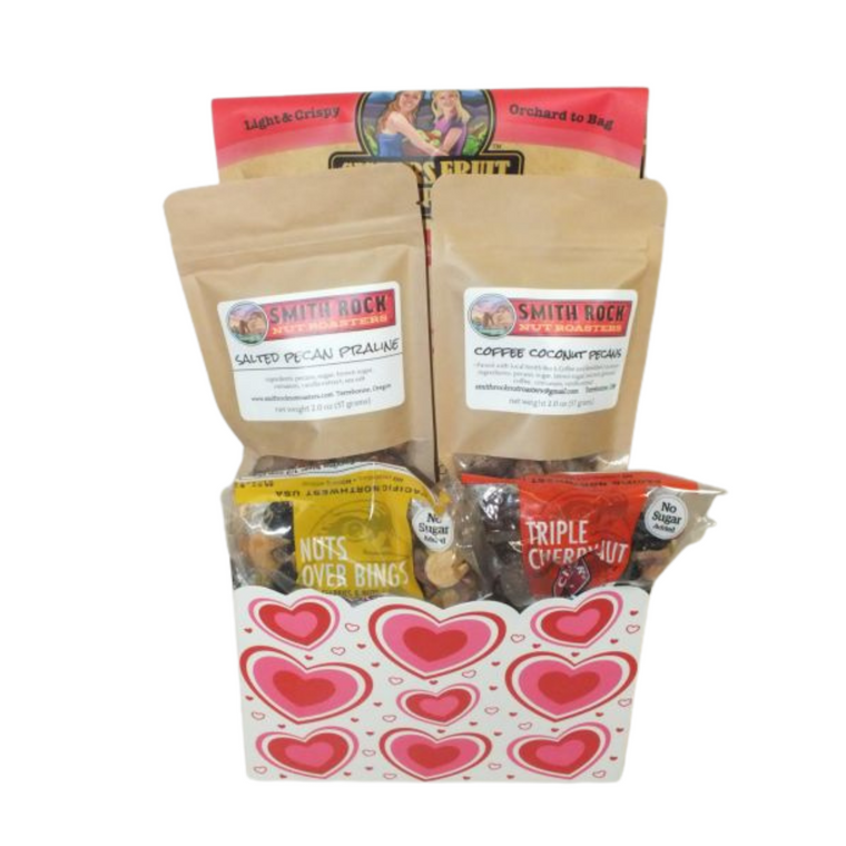 Valentine's Day Northwest Fruit and Nut Sampler includes  Sisters Fruit Company - Apple Chips, Chuckar Cherries - Bings over nut mix, Chuckar Cherries - Triple Cherry Nut mix, Smith Rock Nut Roasters   Coffee Coconut Pecans, Smith Rock Nut Roasters   Salted Pecan Praline.  Designed in recyclable holiday theme container.  Wrapped in Cellophane with handmade bow.
