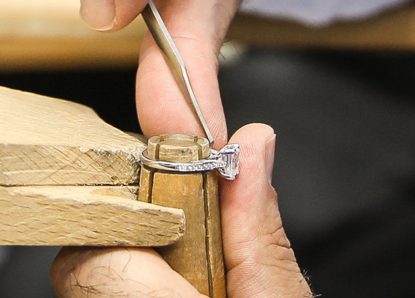 a jewelery craftsman selecting a diamond