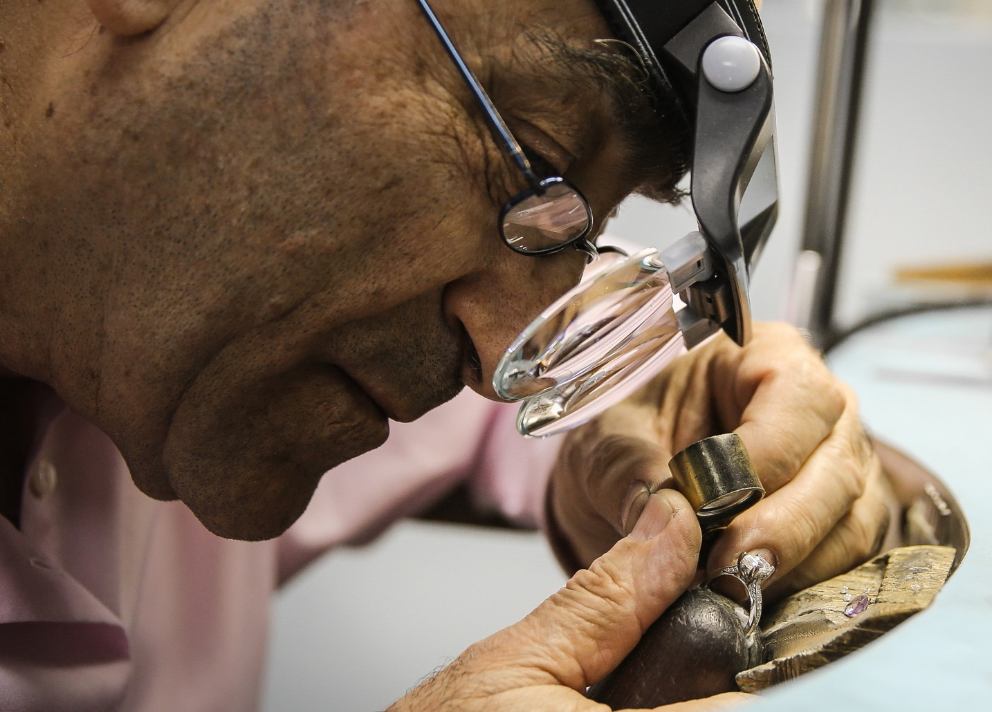 a jewelery craftsman vetting a diamond