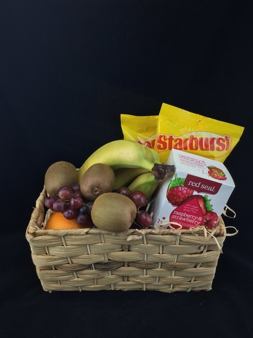 This fresh fruit basket has an extra couple of treats. Fruit Tea, and Starburst lollies.  Fruit baskets are made fresh for delivery.