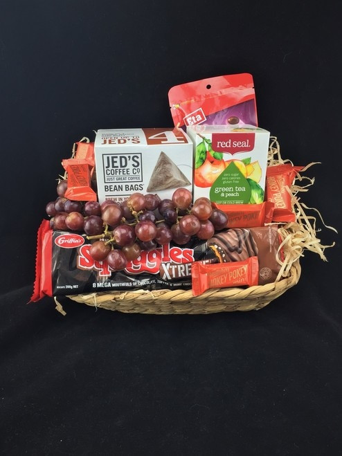 This is a great hamper and very popular. This basket includes Red seal peach green tea, Jeds coffee bags, Seasonal fresh grapes, Squiggles chocolate biscuits, Chocolate peanuts and a  bag of Whittaker's mini slabs (12 included)