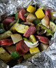 Luxemburg & veggies in foil pouch over campfire.