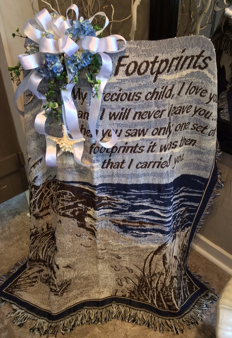 """""""Footprints"""" afghan on easel with silk flowers and starfish"""