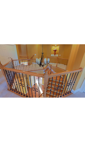decorative staircase with light colored oak and wrought iron balusters