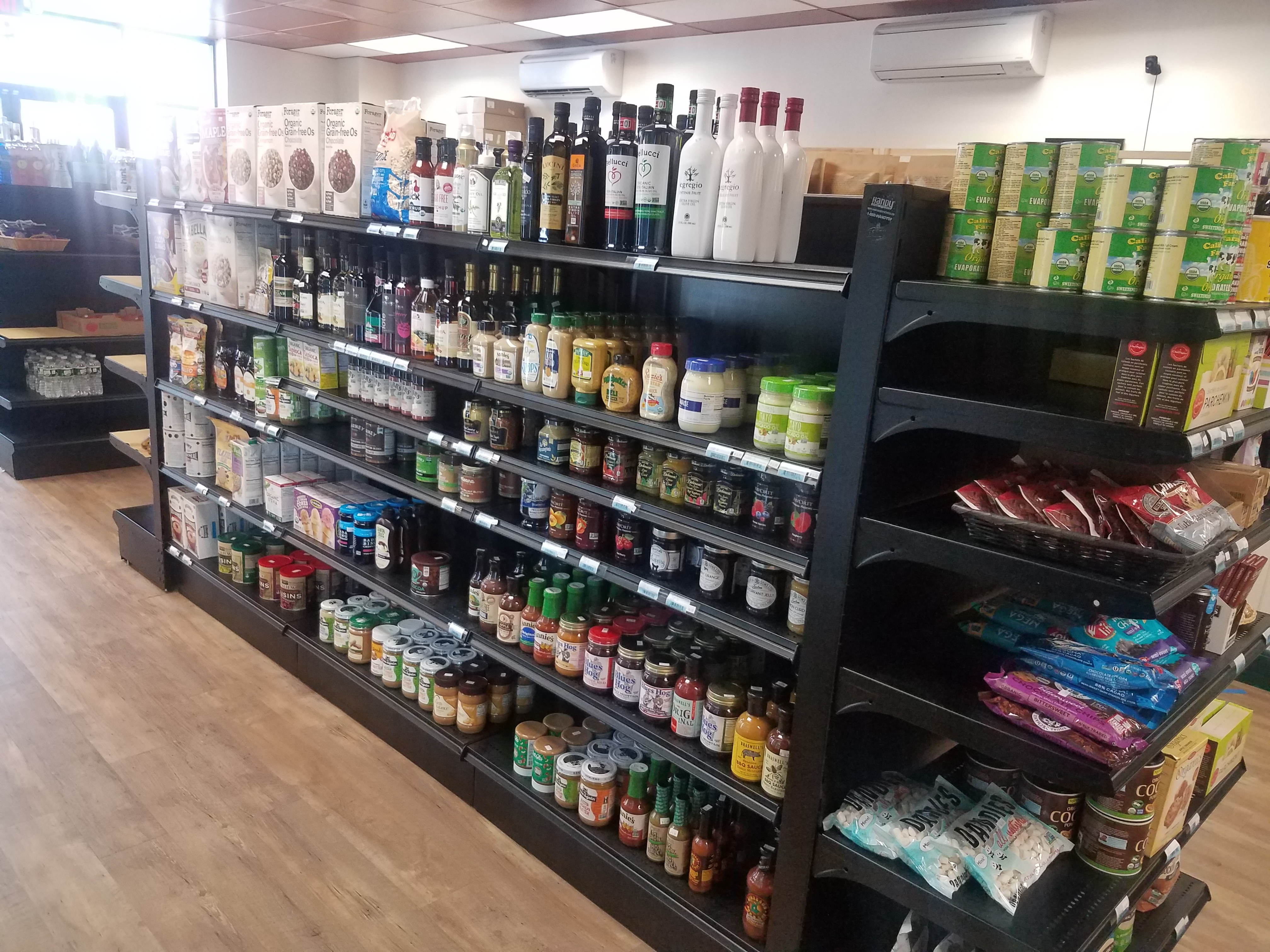 A photo of black shelves, holding various cooking oils, breakfast cereals, nut butters, and jams, as well as baking goods.
