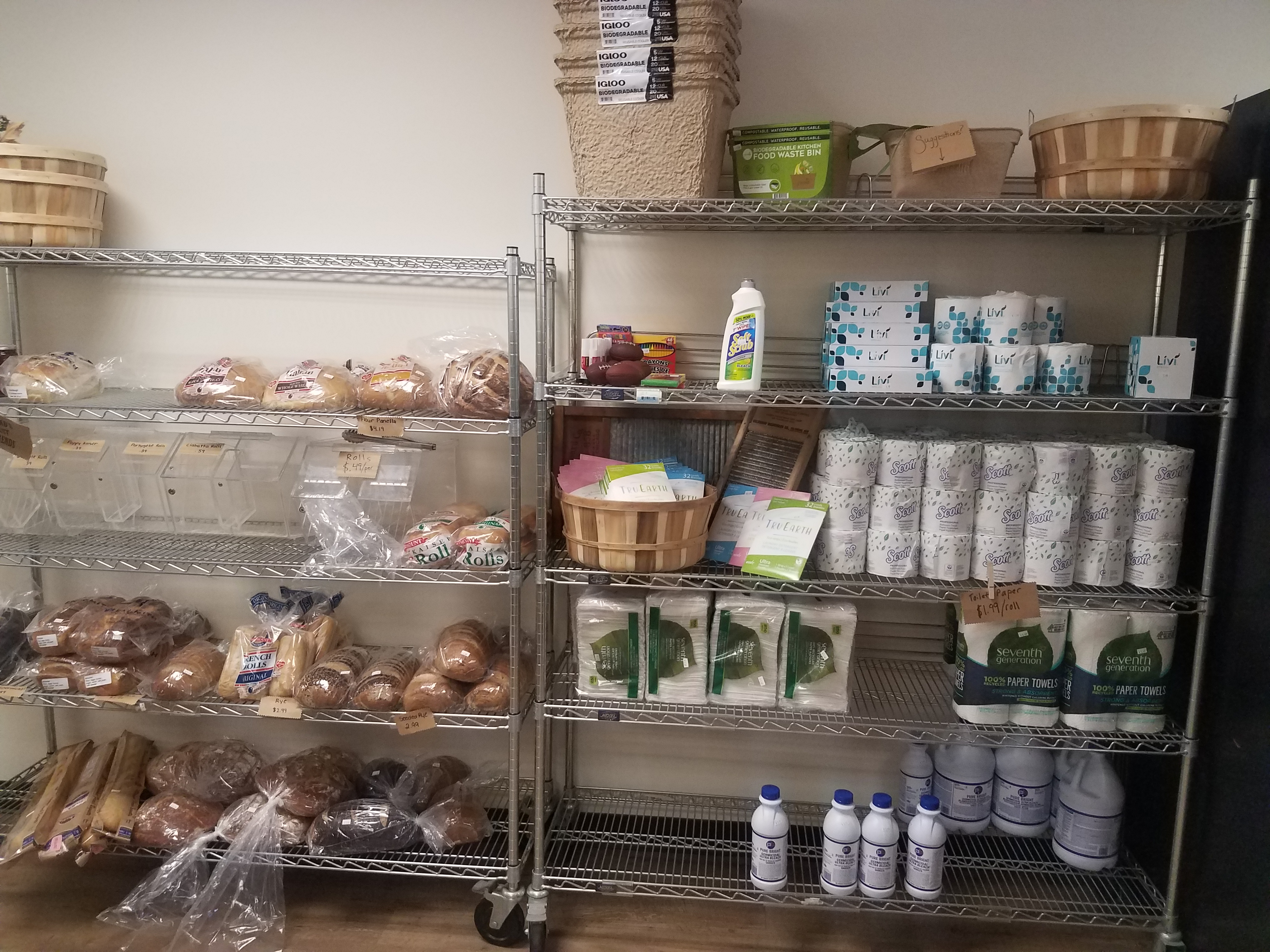A photo of two metal wire racks, one with multiple rows of bread, and one with multiple rows of cleaning supplies. This includes toilet paper, bleach, laundry detergent strips, and gloves.