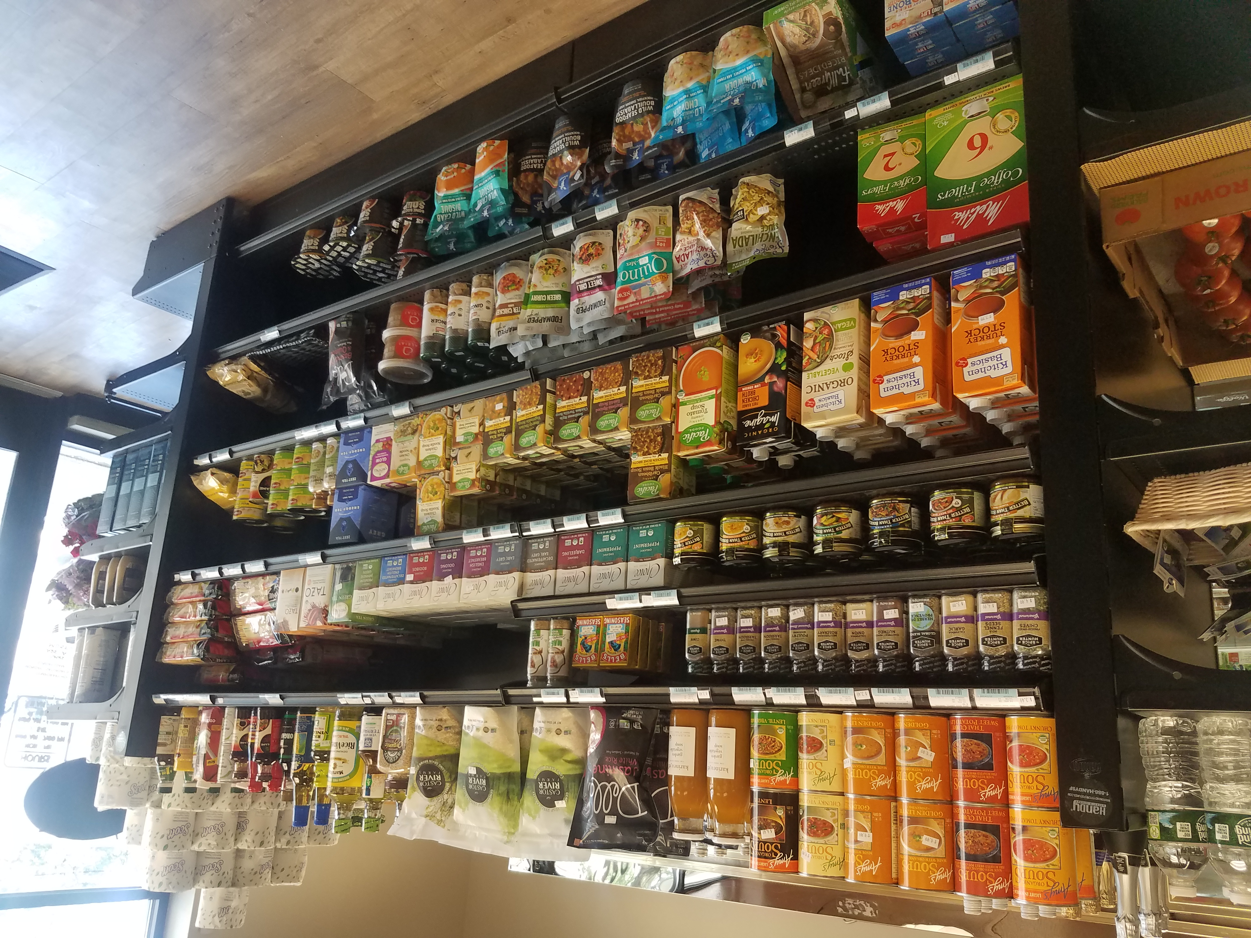 A photo of black shelves housing various canned and packaged soups, bouillons, spices, and rice.