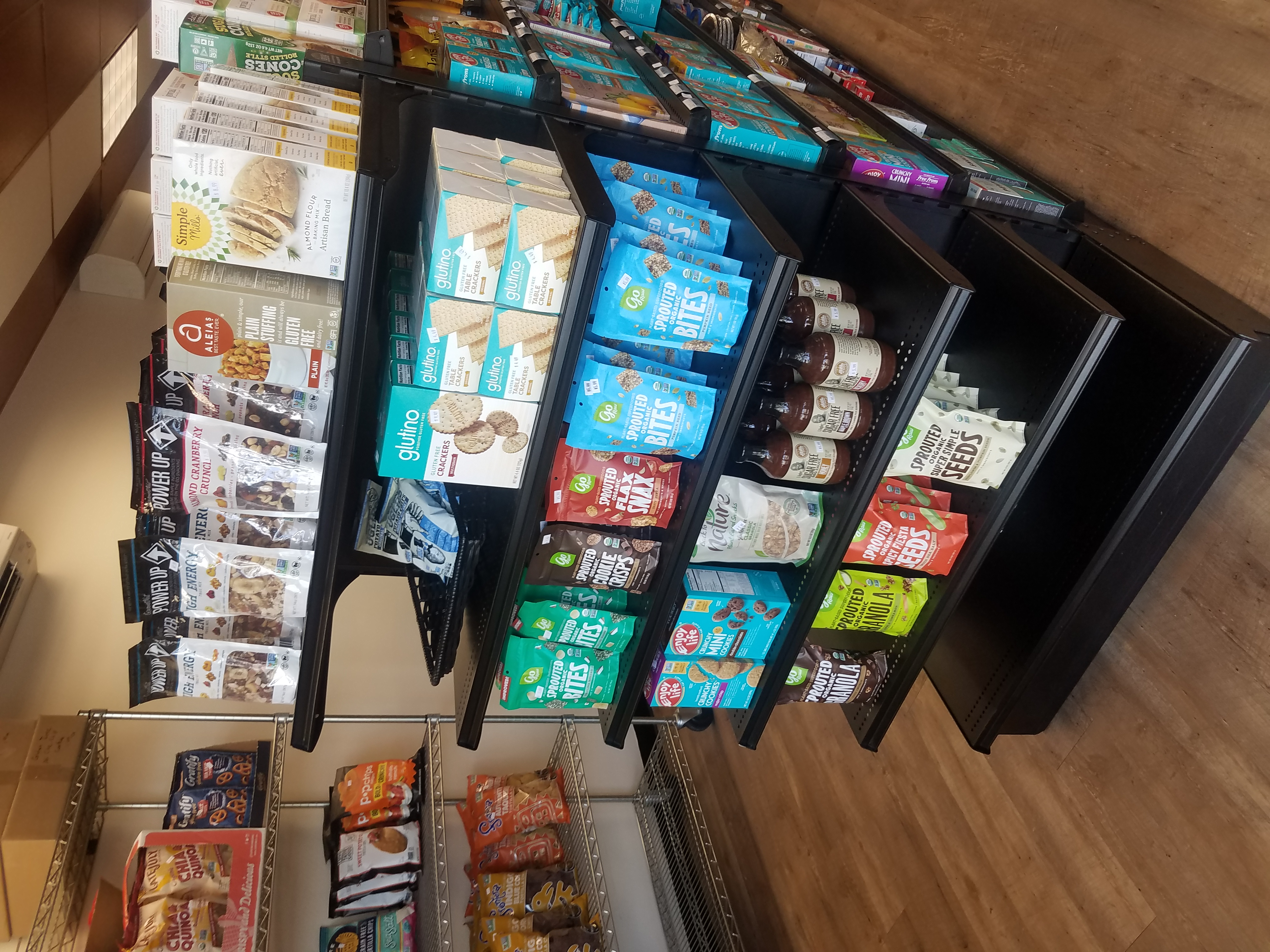 A photo of a black shelf with multiple shelves of gluten free snacks and baked goods.