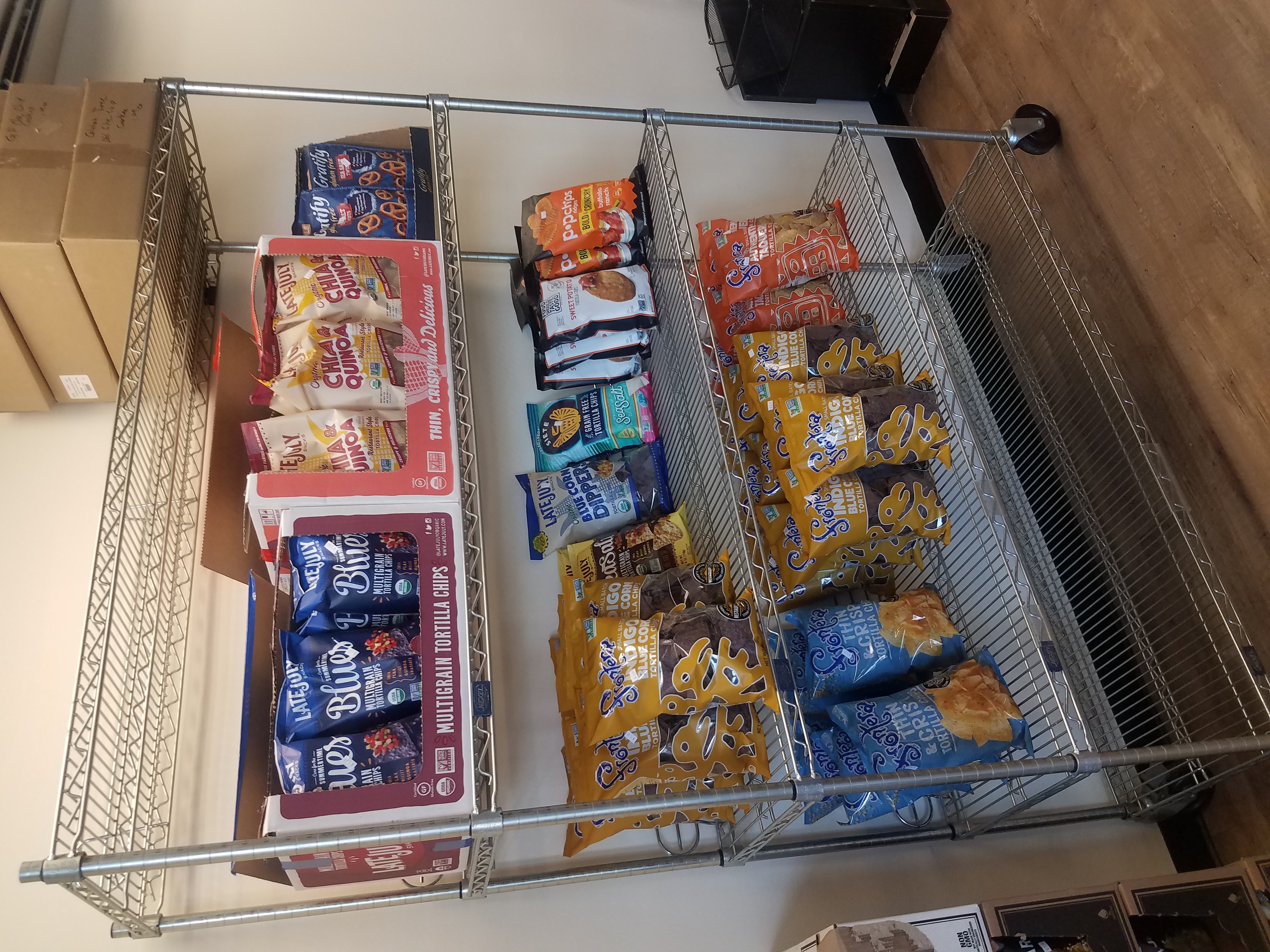 A photo of a metal wire rack with three shelves of bagged chips. Tortilla chips, corn chips, potato chips, and so on.