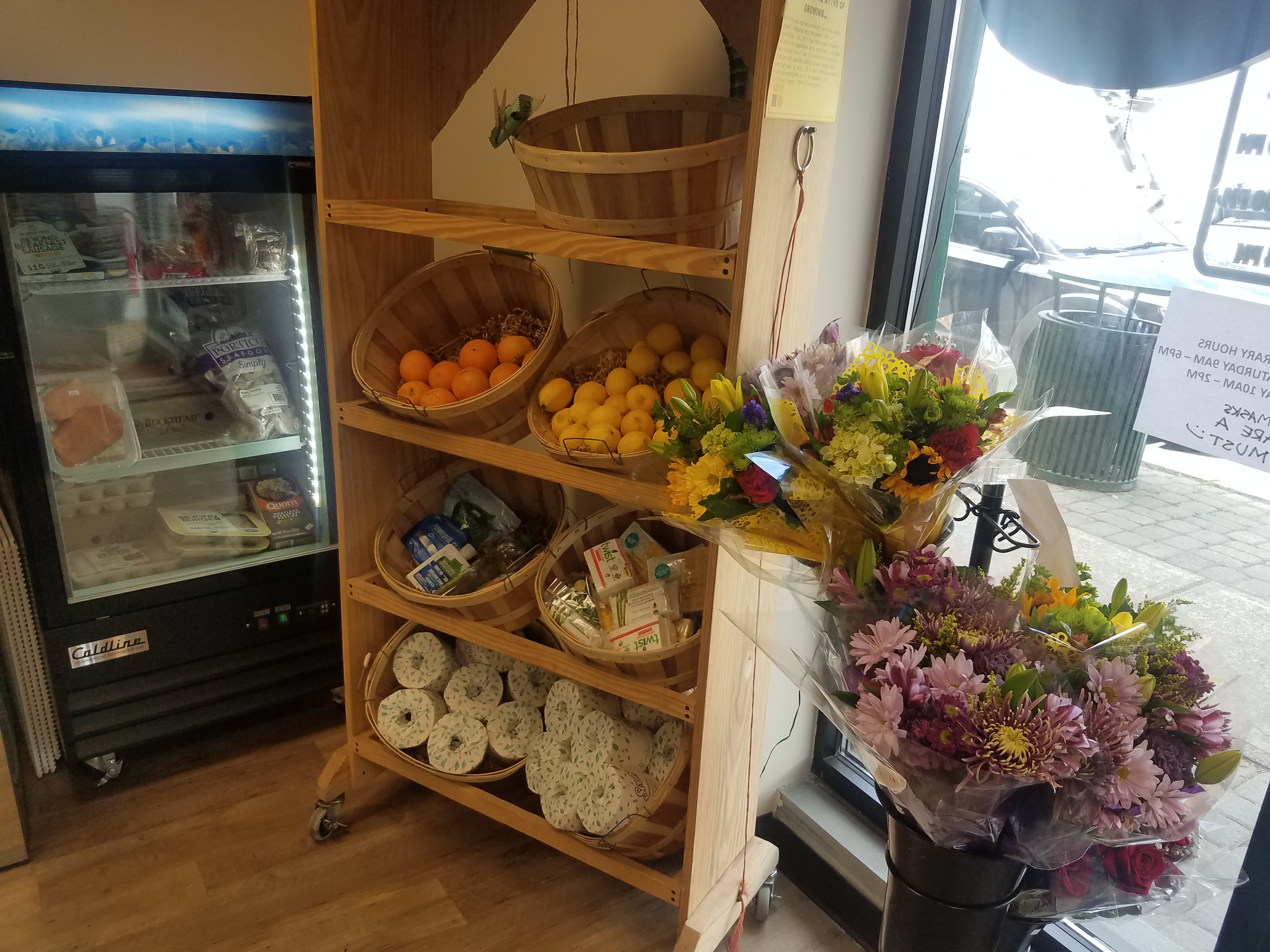 A photo. In the foreground is a metal stand holding multiple bouquets of flowers, in the midground  is a wooden shelf with multiple wicker baskets of fruits and cleaning supplies, and in the background is a freezer. The freezer has a glass door and inside it there are various frozen fishes and meats.