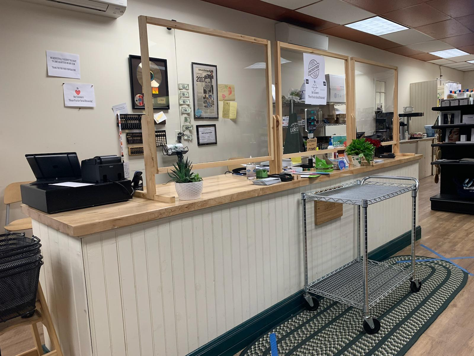 A photo of the check-out counter of a store. There are plexiglass partitions that rise up from the surface of the counter. Also on top of the counter are a cash register, several succulents, and office supplies.