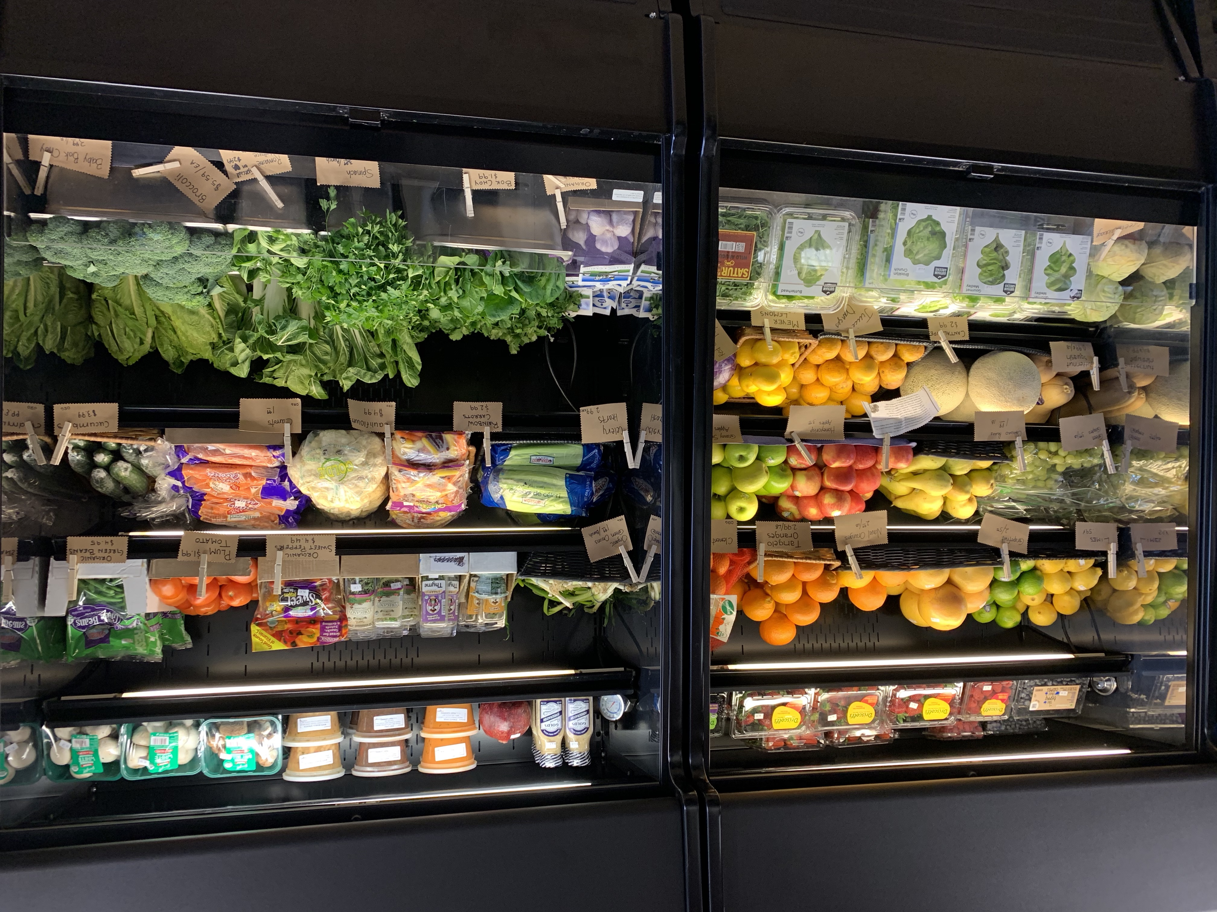 A photo of two black produce fridges with no door. On the shelves are assorted greens and fruits, as well as packaged berries , mushrooms, soups, and herbs.